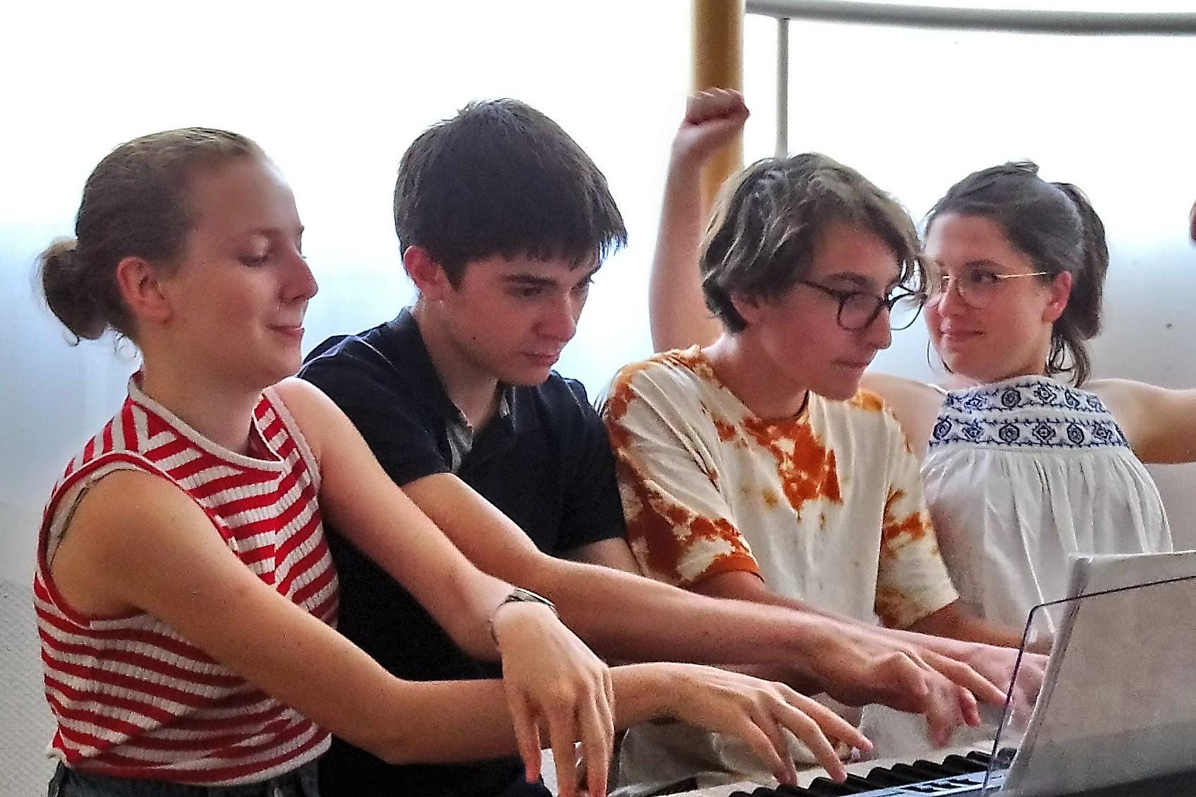 Quatre pianistes jouant sur un piano